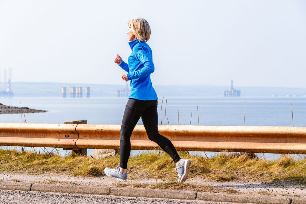 senior-woman-jogging-cromarty-firth-scotland-royalty-free-image-1569270739