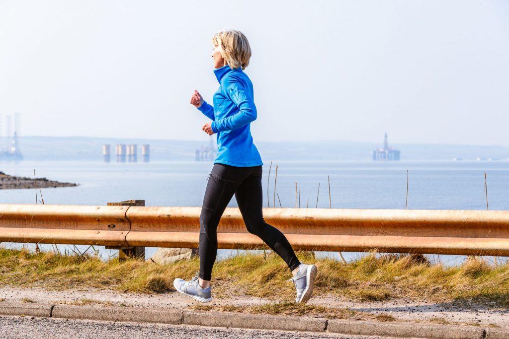 senior-woman-jogging-cromarty-firth-scotland-royalty-free-image-1569270739